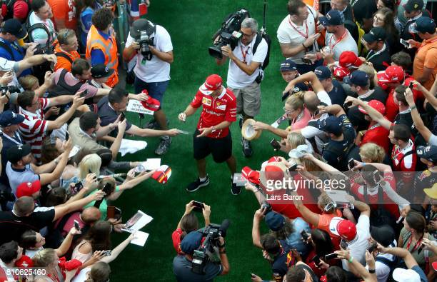 Sebastian Vettel of Germany and Ferrari arrives at the circuit and signs autographs for fans before final practice for the Formula One Grand Prix of...