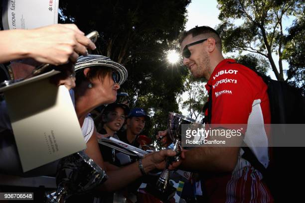 Sebastian Vettel of Germany and Ferrari arrives at the circuit and signs autographs for fans before practice for the Australian Formula One Grand...