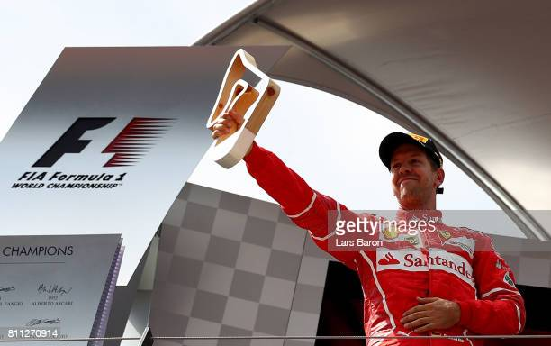 Sebastian Vettel of Germany and Ferrari celebrates finishing in second place on the podium during the Formula One Grand Prix of Austria at Red Bull...