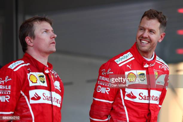 Sebastian Vettel of Germany and Ferrari celebrates his race win on the podium next to Kimi Raikkonen of Finland and Ferrari during the Monaco Formula...