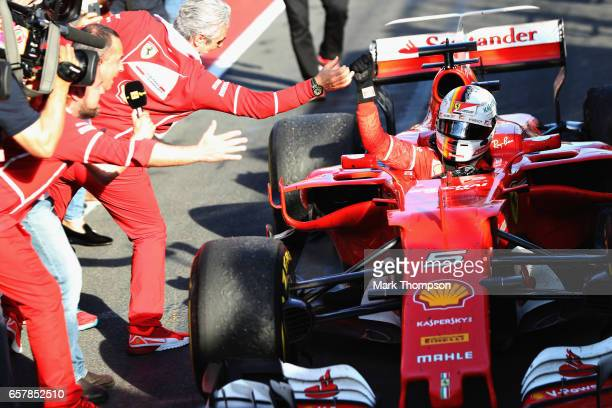 Sebastian Vettel of Germany and Ferrari celebrates his win in parc ferme with Ferrari Team Principal Maurizio Arrivabene during the Australian...