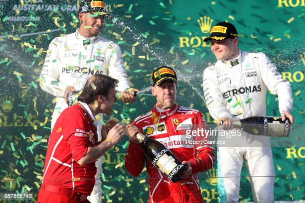 Sebastian Vettel of Germany and Ferrari celebrates his win on the podium with second placed Lewis Hamilton of Great Britain and Mercedes GP and...