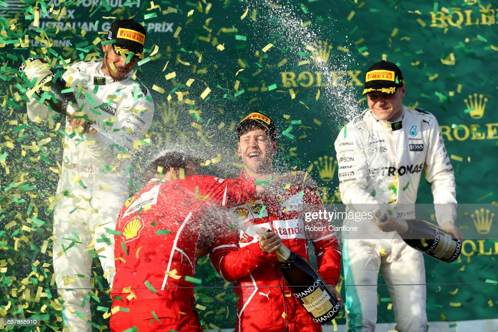 Sebastian Vettel of Germany and Ferrari celebrates his win on the podium with second placed Lewis Hamilton of Great Britain and Mercedes GP and Valtteri Bottas of Finland and Mercedes GP during the Australian Formula One Grand Prix at Albert Park on March 26, 2017 in Melbourne, Australia.