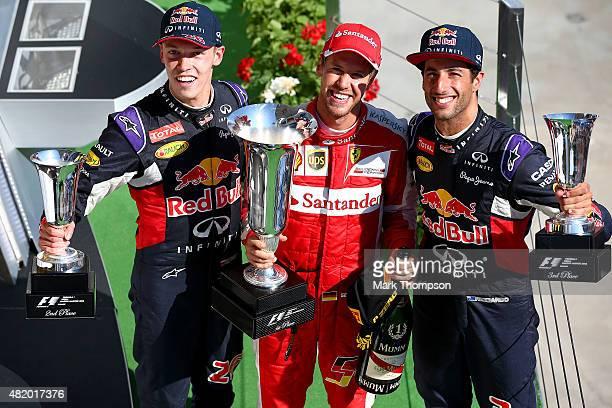 Sebastian Vettel of Germany and Ferrari celebrates on the podium next to Daniel Ricciardo of Australia and Infiniti Red Bull Racing Daniil Kvyat of...