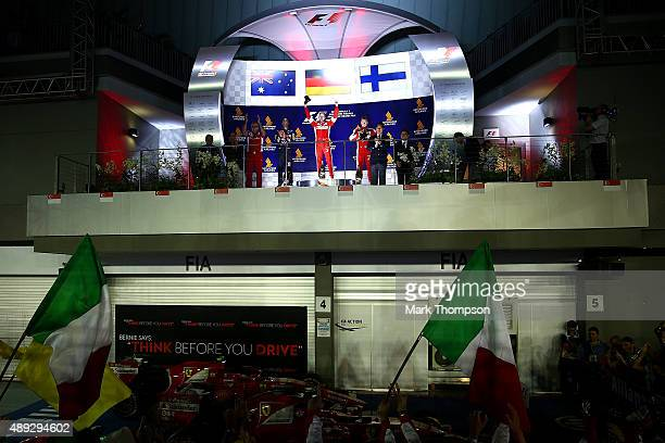 Sebastian Vettel of Germany and Ferrari celebrates on the podium next to Daniel Ricciardo of Australia and Infiniti Red Bull Racing and Kimi...