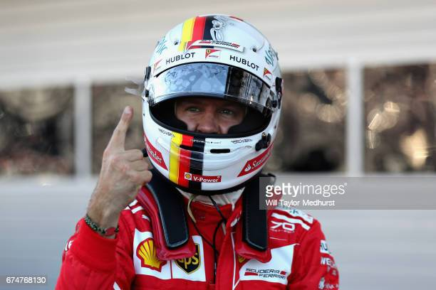 Sebastian Vettel of Germany and Ferrari celebrates qualifying in pole position in parc ferme during qualifying for the Formula One Grand Prix of...