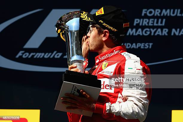 Sebastian Vettel of Germany and Ferrari celebrates with the trophy on the podium after winning the Formula One Grand Prix of Hungary at Hungaroring...