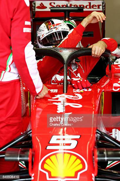 Sebastian Vettel of Germany and Ferrari climbs into his car fitted with the halo in the garage during practice for the Formula One Grand Prix of...
