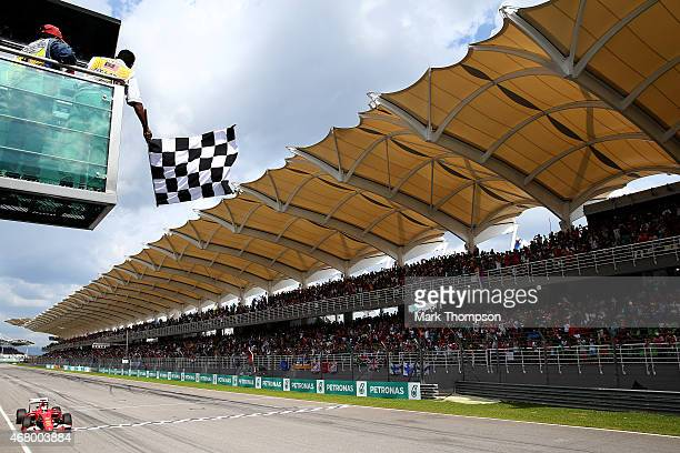 Sebastian Vettel of Germany and Ferrari crosses the finish line and takes the checkered flag as he wins the Malaysia Formula One Grand Prix at Sepang...