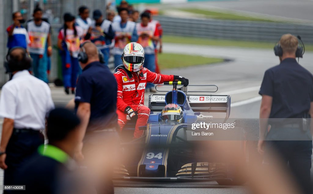 Sebastian Vettel of Germany and Ferrari gets a ride from Pascal Wehrlein of Germany driving the (94) Sauber F1 Team Sauber C36 Ferrari after stopping on track during the Malaysia Formula One Grand Prix at Sepang Circuit on October 1, 2017 in Kuala Lumpur, Malaysia.