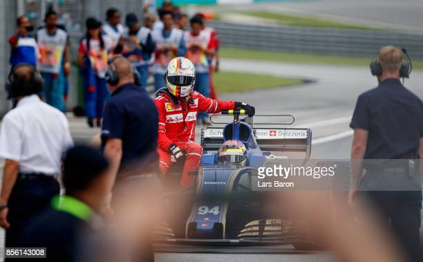 Sebastian Vettel of Germany and Ferrari gets a ride from Pascal Wehrlein of Germany driving the Sauber F1 Team Sauber C36 Ferrari after stopping on...