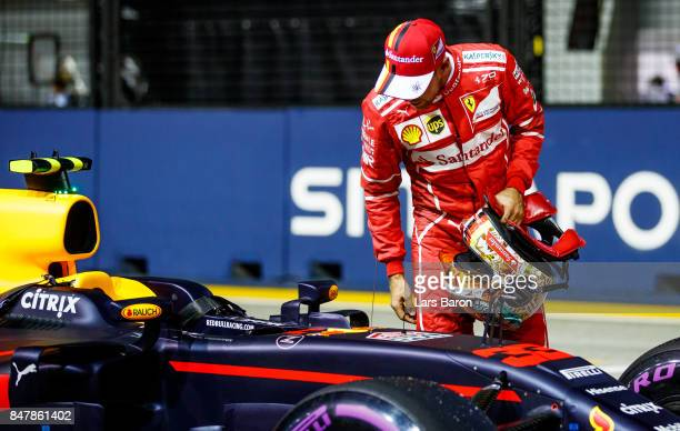 Sebastian Vettel of Germany and Ferrari inspects the car of Max Verstappen of Netherlands and Red Bull Racing in parc ferme after qualifying for the...