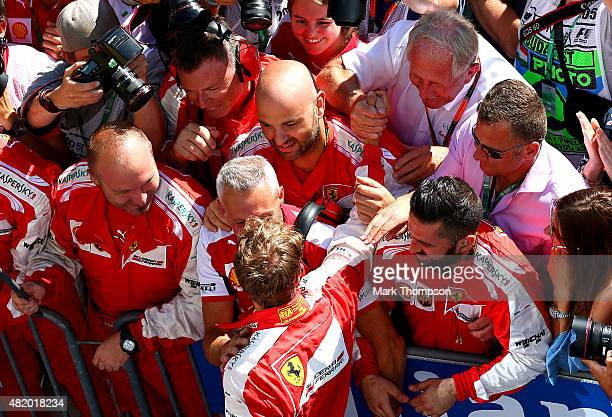 Sebastian Vettel of Germany and Ferrari is congratulated by Infiniti Red Bull Racing Team Consultant Dr Helmut Marko in Parc Ferme after winning the...