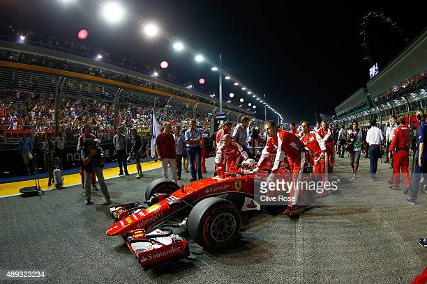 Sebastian Vettel of Germany and Ferrari is pushed into position on the grid before the Formula One Grand Prix of Singapore at Marina Bay Street...