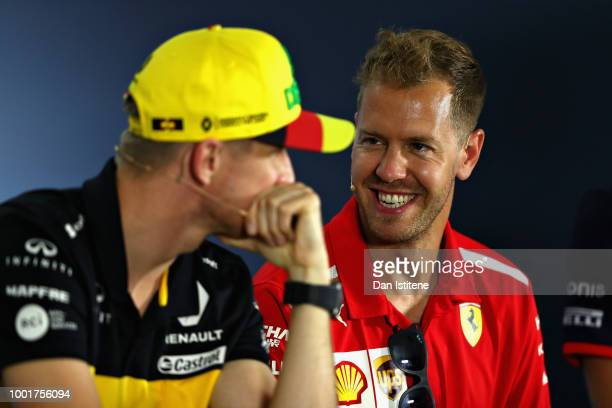 Sebastian Vettel of Germany and Ferrari jokes with Nico Hulkenberg of Germany and Renault Sport F1 in the Drivers Press Conference during previews...