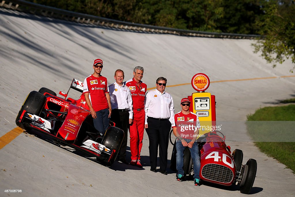 Sebastian Vettel of Germany and Ferrari, Kimi Raikkonen of Finland and Ferrari, Ferrari Team Principal Maurizio Arrivabene, Istvan Kapitany and John Abbott pose next to the 2015 and 1951 cars on the old Monza banking after qualifying for the Formula One Grand Prix of Italy at Autodromo di Monza on September 5, 2015 in Monza, Italy.