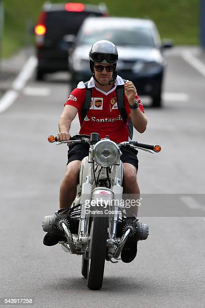Sebastian Vettel of Germany and Ferrari leaves the circuit on a motorbike during previews ahead of the Formula One Grand Prix of Austria at Red Bull...