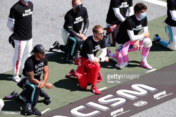 Sebastian Vettel of Germany and Ferrari Lewis Hamilton of Great Britain and Mercedes GP and Lance Stroll of Canada and Racing Point take a knee in...