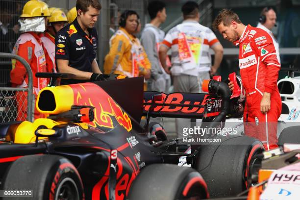 Sebastian Vettel of Germany and Ferrari looks at the car of Daniel Ricciardo of Australia and Red Bull Racing in parc ferme during qualifying for the...