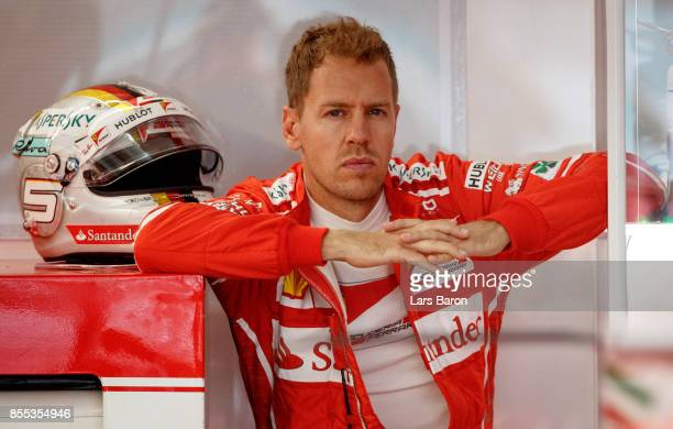 Sebastian Vettel of Germany and Ferrari looks on from the garage during practice for the Malaysia Formula One Grand Prix at Sepang Circuit on...