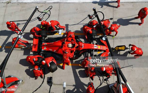 Sebastian Vettel of Germany and Ferrari makes a pit stop for new tyres during the Formula One Grand Prix of China at Shanghai International Circuit...
