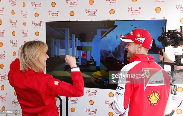 Sebastian Vettel of Germany and Ferrari plays the 'Unleashed' video game against a member of the audience at the Shell VPower Nitro Fan Fest on...