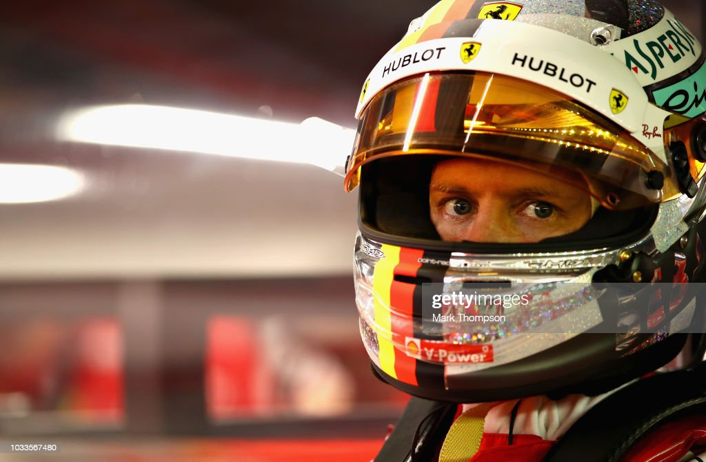 Sebastian Vettel of Germany and Ferrari prepares to drive in the garage during qualifying for the Formula One Grand Prix of Singapore at Marina Bay Street Circuit on September 15, 2018 in Singapore.