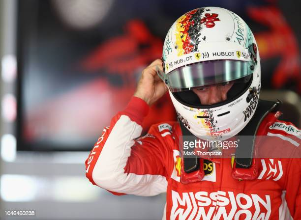 Sebastian Vettel of Germany and Ferrari prepares to drive in the garage during qualifying for the Formula One Grand Prix of Japan at Suzuka Circuit...