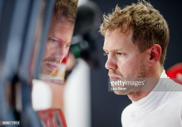 Sebastian Vettel of Germany and Ferrari prepares to drive in the garage during practice for the Formula One Grand Prix of Japan at Suzuka Circuit on...