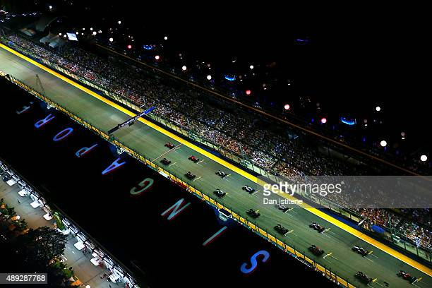 Sebastian Vettel of Germany and Ferrari pulls away from the start ahead of Daniel Ricciardo of Australia and Infiniti Red Bull Racing Kimi Raikkonen...
