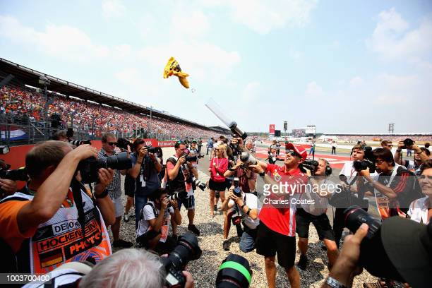 Sebastian Vettel of Germany and Ferrari shoots tshirts into the crowd at the drivers parade before the Formula One Grand Prix of Germany at...