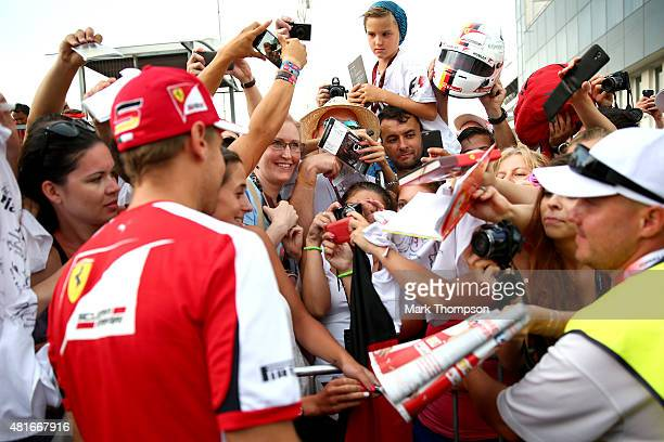 Sebastian Vettel of Germany and Ferrari signs autographs for fans at a signing session during previews to the Formula One Grand Prix of Hungary at...