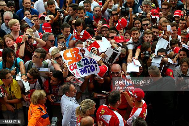 Sebastian Vettel of Germany and Ferrari signs autographs for fans in the pit lane during previews to the Formula One Grand Prix of Italy at Autodromo...