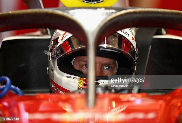 Sebastian Vettel of Germany and Ferrari sits in his car fitted with the halo in the garage during practice for the Abu Dhabi Formula One Grand Prix...