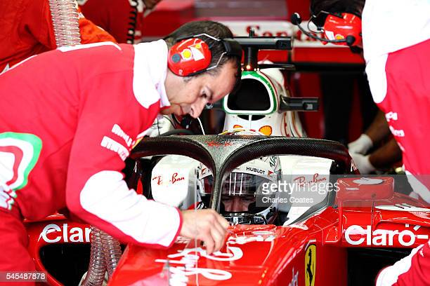 Sebastian Vettel of Germany and Ferrari sits in his car in the garage with the halo fitted during practice for the Formula One Grand Prix of Great...
