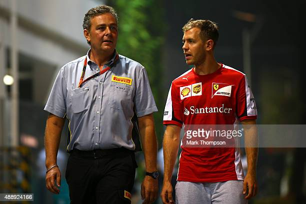 Sebastian Vettel of Germany and Ferrari speaks with Mario Isola Pirelli's engineer at Ferrari in the paddock after practice for the Formula One Grand...