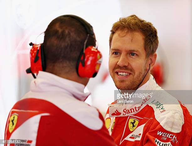Sebastian Vettel of Germany and Ferrari talks to a member of the Scuderia Ferrari team in the garage during final practice for the United States...