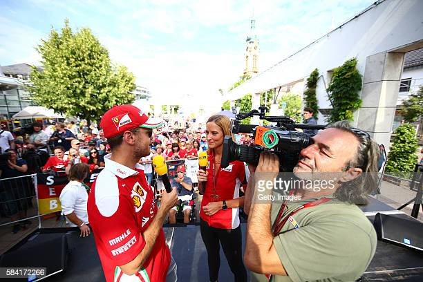 Sebastian Vettel of Germany and Ferrari talks to Anna Fleischhauer of RTL TV on stage at the Shell fan quiz event during the Formula One Grand Prix...