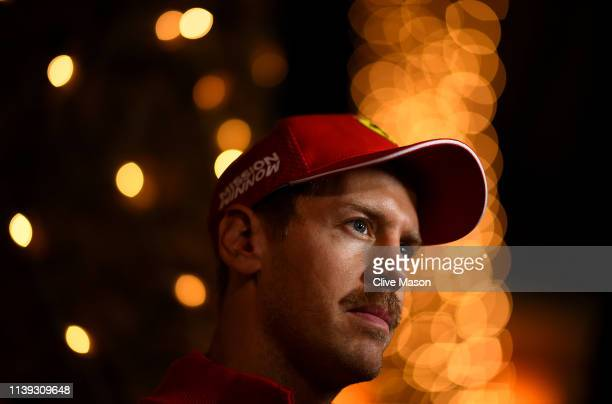 Sebastian Vettel of Germany and Ferrari talks to the media in the Paddock after qualifying for the F1 Grand Prix of Bahrain at Bahrain International...