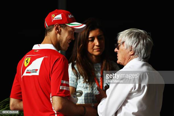 Sebastian Vettel of Germany and Ferrari talks with Bernie Ecclestone, Chairman Emeritus of the Formula One Group and his wife Fabiana before the...