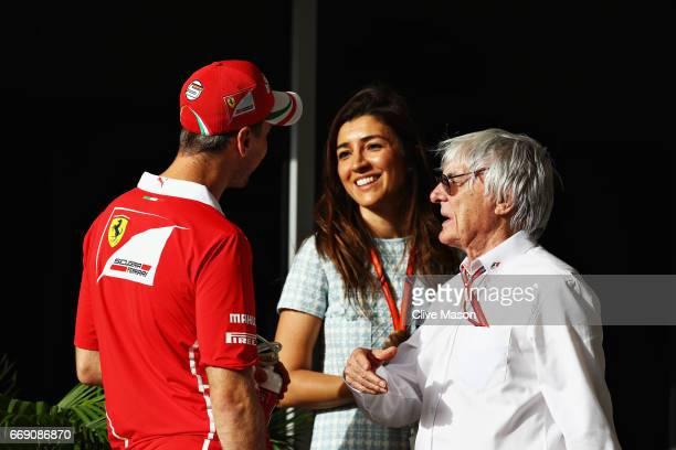 Sebastian Vettel of Germany and Ferrari talks with Bernie Ecclestone Chairman Emeritus of the Formula One Group and his wife Fabiana before the...