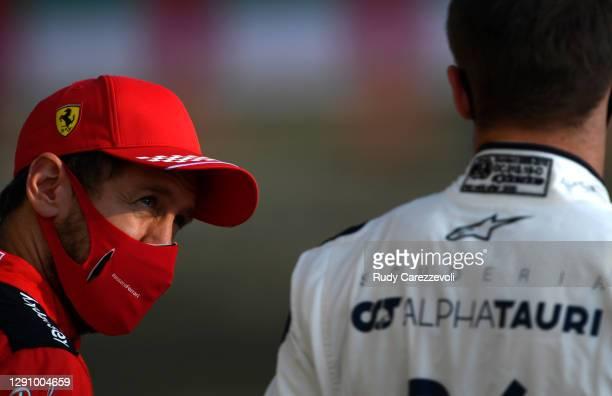 Sebastian Vettel of Germany and Ferrari talks with Daniil Kvyat of Russia and Scuderia AlphaTauri on the grid prior to the F1 Grand Prix of Abu Dhabi...