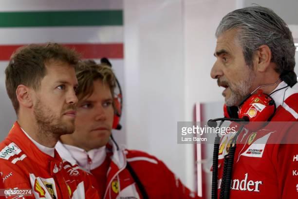 Sebastian Vettel of Germany and Ferrari talks with Ferrari Team Principal Maurizio Arrivabene in the garage during practice for the Formula One Grand...