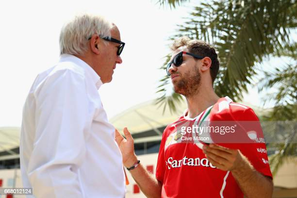 Sebastian Vettel of Germany and Ferrari talks with FIA Race Director Charlie Whiting in the Paddock during previews to the Bahrain Formula One Grand...