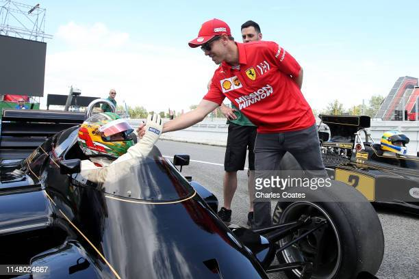 Sebastian Vettel of Germany and Ferrari talks with Joaquin Folch in a classic Lotus F1 car during previews ahead of the F1 Grand Prix of Spain at...