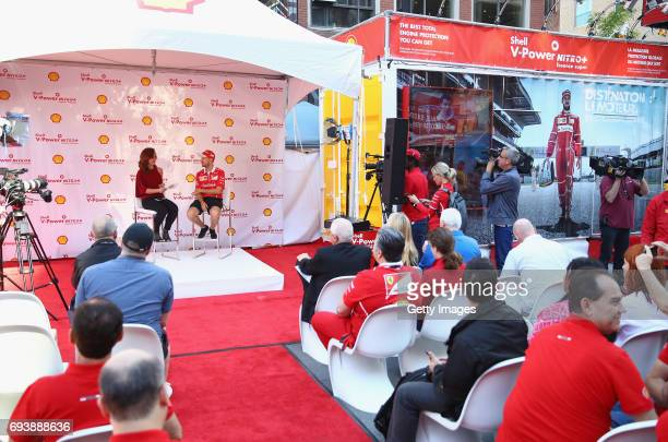 Sebastian Vettel of Germany and Ferrari talks with Kate Beirness at a Shell event during previews for the F1 Grand Prix of Canada at Circuit Gilles...