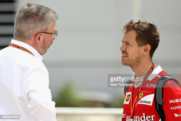 Sebastian Vettel of Germany and Ferrari talks with Ross Brawn Managing Director of the Formula One Group in the Paddock before the Bahrain Formula...