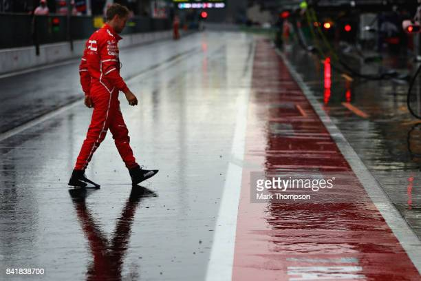 Sebastian Vettel of Germany and Ferrari walks in the Pitlane during qualifying for the Formula One Grand Prix of Italy at Autodromo di Monza on...