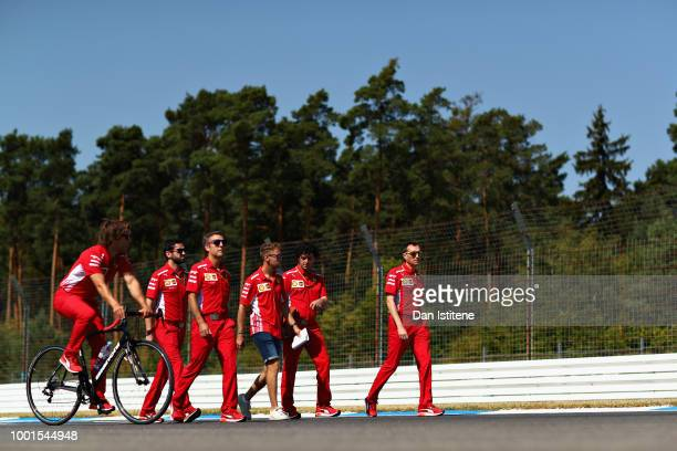 Sebastian Vettel of Germany and Ferrari walks the track with his team during previews ahead of the Formula One Grand Prix of Germany at...
