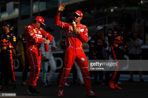 Sebastian Vettel of Germany and Ferrari waves to the crowd on the drivers parade before the Abu Dhabi Formula One Grand Prix at Yas Marina Circuit on...